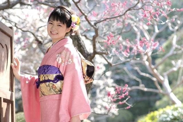 桜の木の下でほほ笑む女性